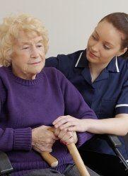 donna anziana col bastone viene assistita dal personale