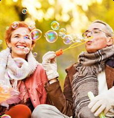 anziana coppia gioca con le bolle di sapone