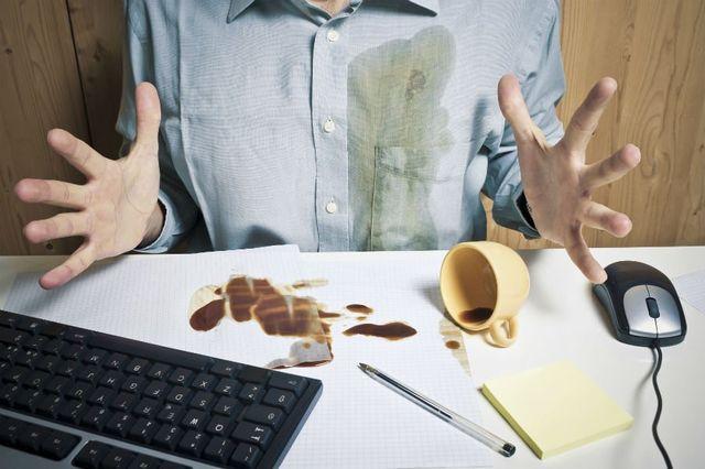 due mani di un uomo che ha rovesciato una tazza di caffè sulla camicia