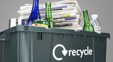 A recycling box full of bottles, cans and papers