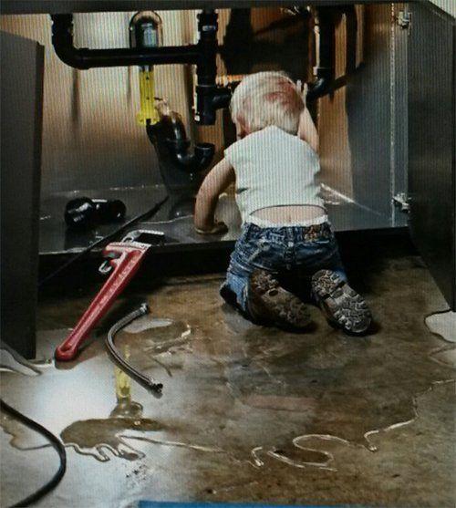 Young kid watching the plumbing repair