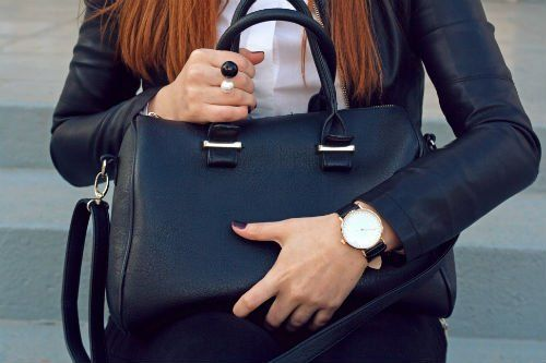 Donna abbracciando una borsetta nera