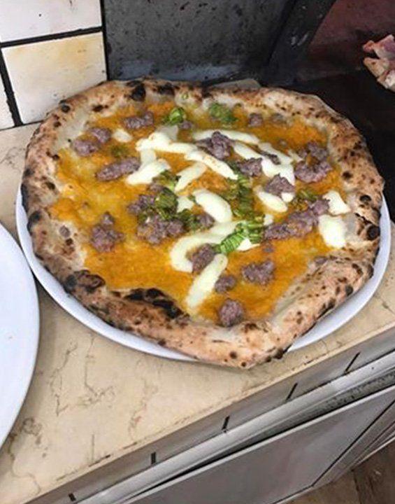 pizza con crema di zucca salsiccia e mozzarella