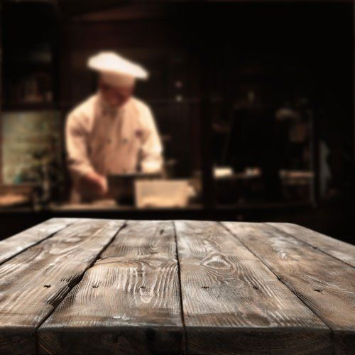 interno del ristorante e cucina con nel fondo lo chef che cucina