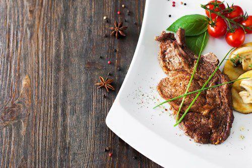 gustosa bistecca con pomodoro sullo sfondo di legno