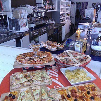 Un tavolo con delle pizze di diversi gusti esposte su dei piatti e dietro il bancone del bar con macchina del caffè, e mobili a muro di color bianco con sopra delle bottiglie di liquori esposte