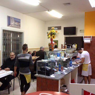 interno della pizzeria con delle persone sedute ai tavoli, un cameriere visto dal dietro con un grembiule giallo con un piatto di pizza in mano e sulla destra un pizzaiolo dietro al bancone che sta stendendo l'impasto con un mattarello