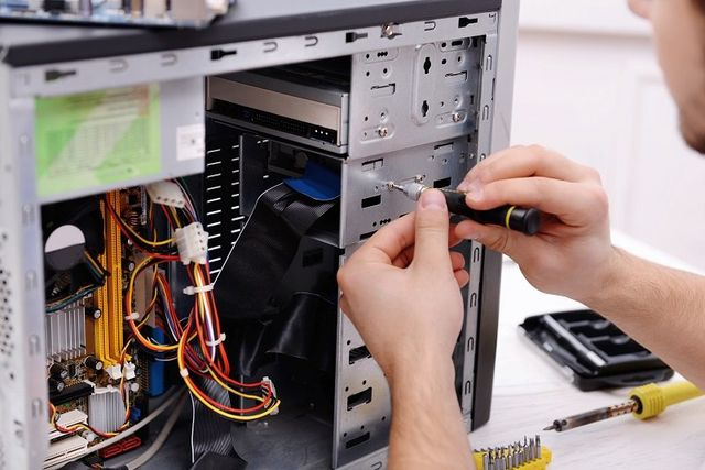 un ragazzo che con un cacciavite sta smontando l'alloggio hard disk di un computer