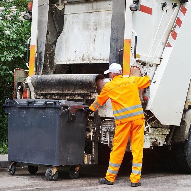 un uomo e di fianco un camion dei rifiuti e un cassonetto