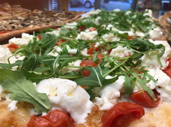 una pizza con pomodorini rucola e mozzarella