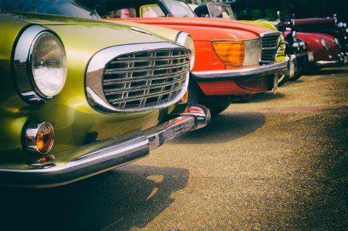 una serie di macchine vintage parcheggiate in fila