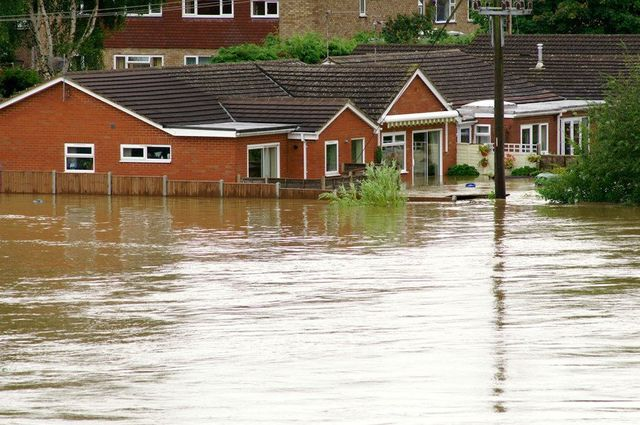 A flooded street, with water halfway up the outside of the houses