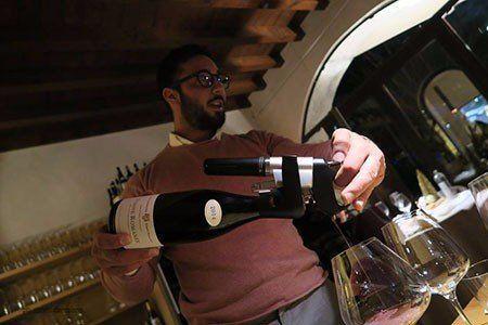 un uomo mentre serve il vino in due bicchieri