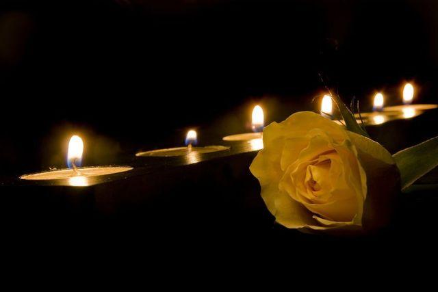 una rosa e dei ceri accesi