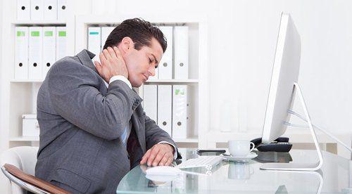 uomo seduto alla scrivania di un ufficio con dolore al collo