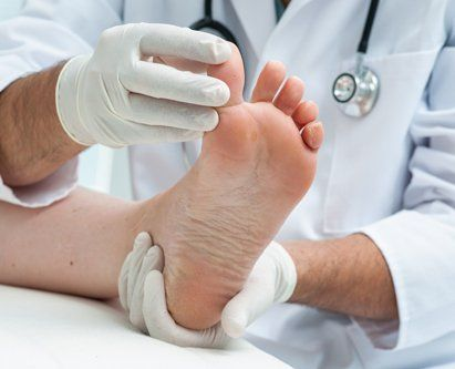 Professional podiatrist examining patient's thumb