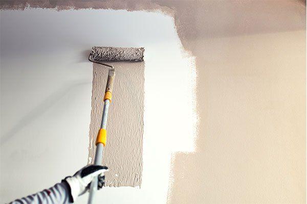una mano con un rullo che imbianca un muro di grigio