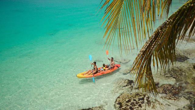 A family uses a kayak in Grand Case