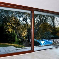 una porta finestra scorrevole marrone con vista degli alberi e della piscina all'esterno