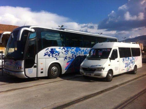 un bus per viaggi e un furgoncino in un parcheggio