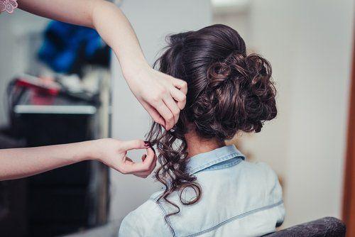 parrucchiera sistema acconciatura ad una cliente con capelli scuri