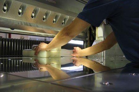 due mani di un uomo vicino a un macchinario che stampa etichette
