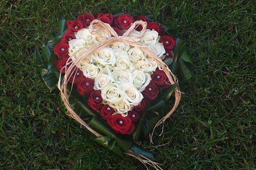 Corona di fiori in forma di cuore di rose rosse e bianche