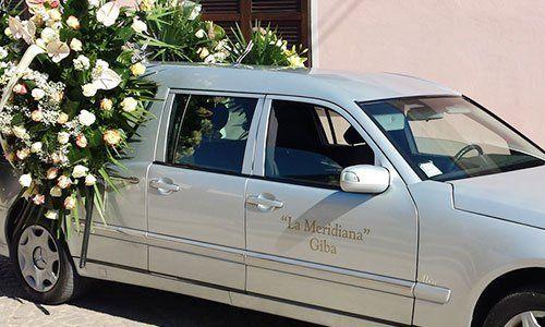 Auto funebre di colore grigio con la parte posteriore coperta di fiori