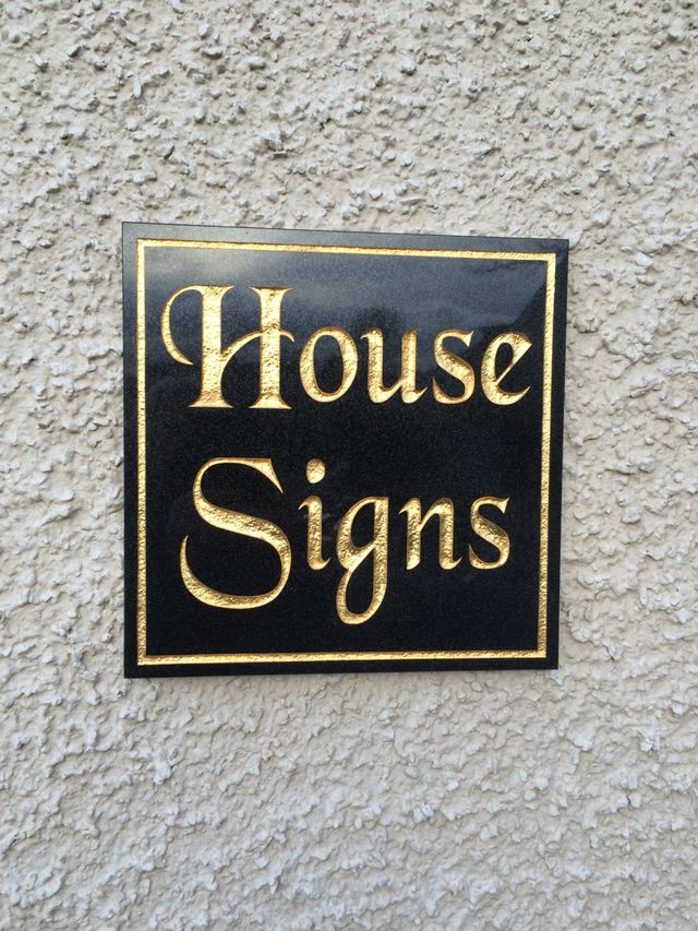 square granite house sign with border and lettering embellished in gold