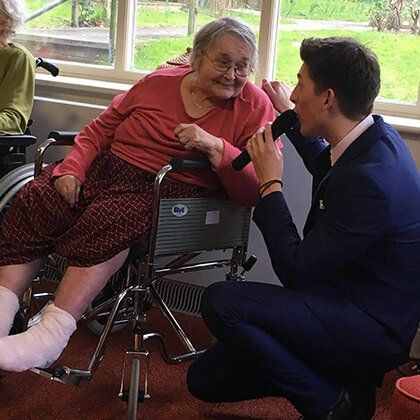 James next to an elderly woman during one of their shows