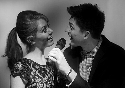 young couple singing a song together during one of their shows