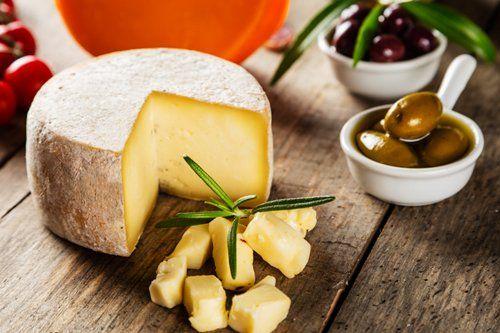 pezzo di formaggio tagliato con olive  a contorno