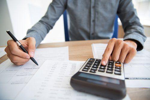 uomo mentre fa dei conti con la calcolatrice e scrive su dei documenti