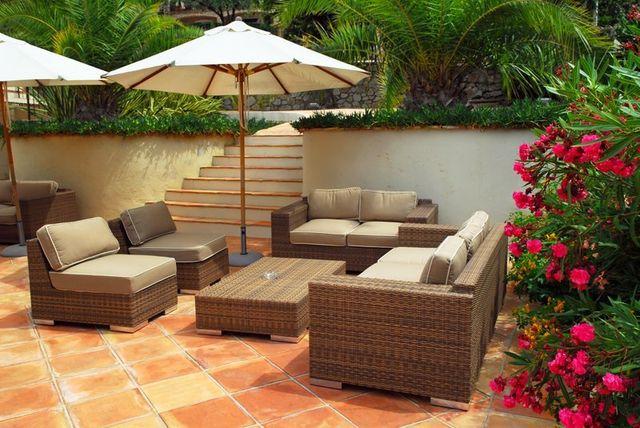 zona relax di un giardino con poltrone divani e ombrellone.
