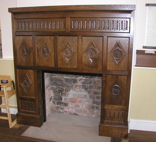 Large wooden fireplace with engravings