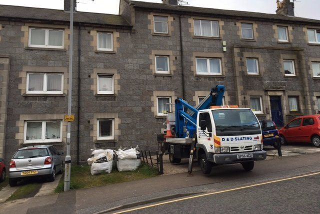 A cherry picker in front of a building