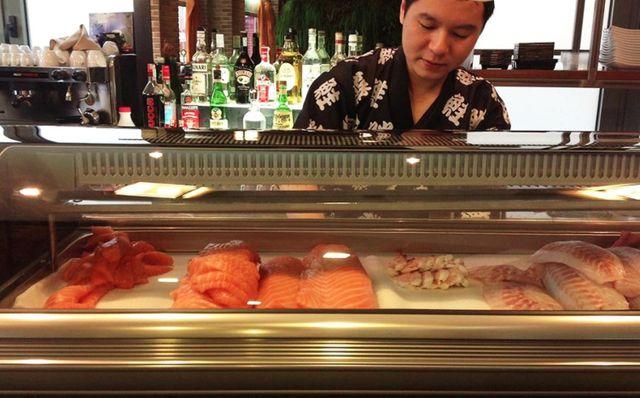 Chef giapponese sceglie del salmone al ristorante Il Paradiso Del Sushi a Pavia