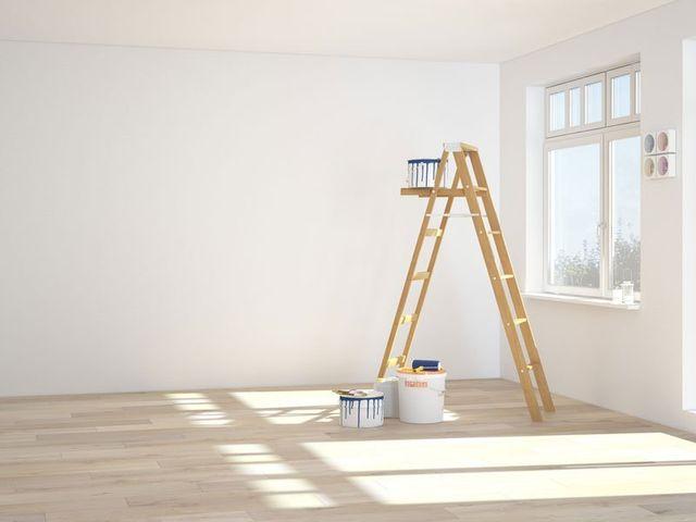 una stanza imbiancata , una scala in legno e dei secchi di pittura