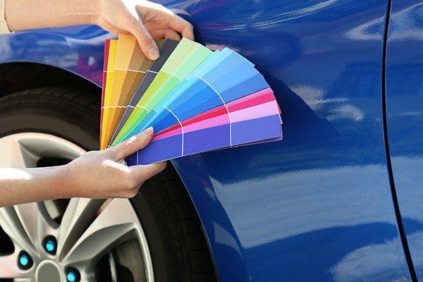 Mano con una lettera di colori per scegliere il nuovo colore dell'automobile