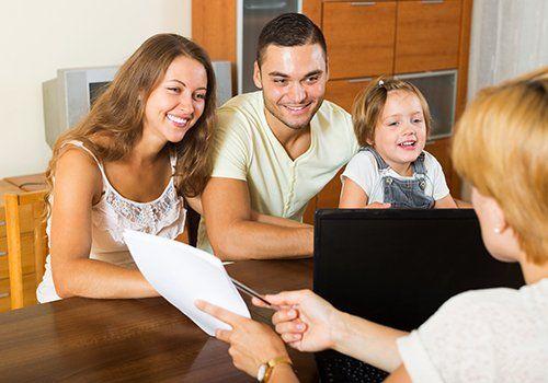 consulente mostra un foglio a una famiglia durante una consulenza
