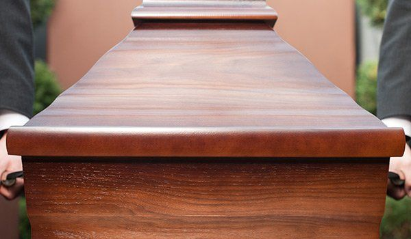 una bara in legno e si intravedono due mani che la sorreggono su entrambi i lati