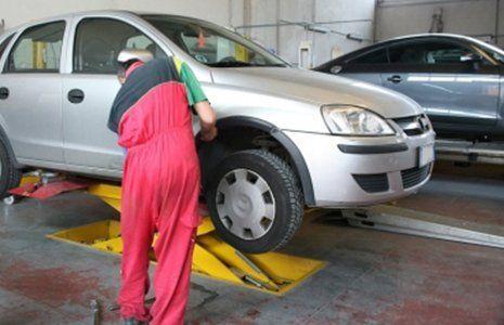 meccanico che ripara una macchina in una officina