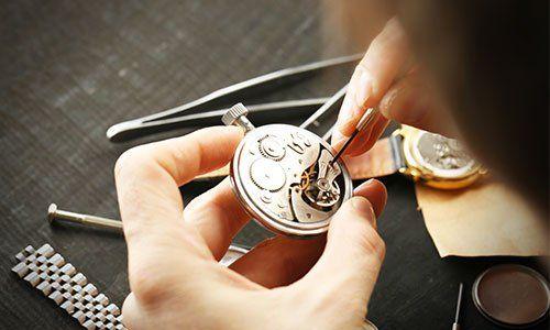 due mani che riparano un orologio da polso