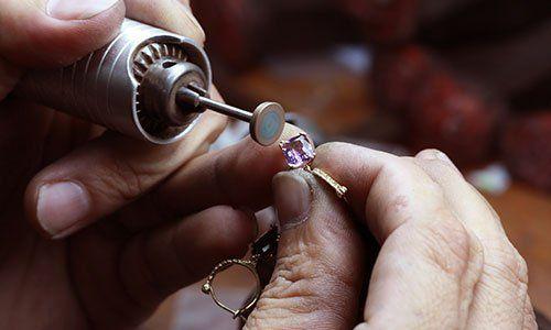 due mani con in mano un oggetto di metallo e nell'altra un gioiello con una pietra viola