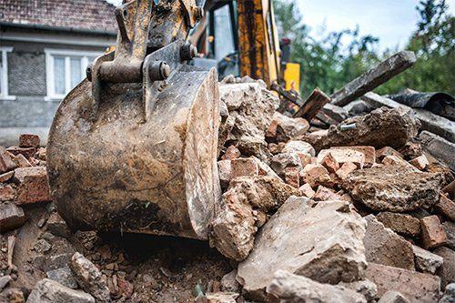 vista della pala di una scavatrice che scava tra le macerie di pietra