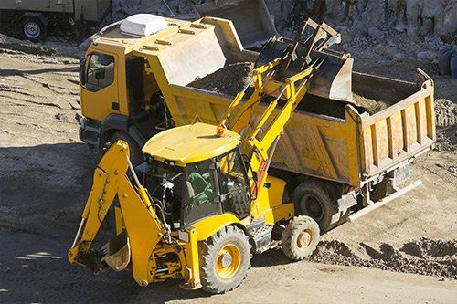una scavatrice di color giallo sta caricando della terra nel rimorchio di un camion da lavoro