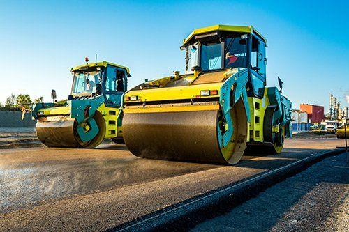 due mezzi asfaltatori di color giallo al lavoro su una strada