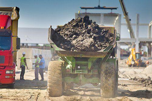 vista di un mezzo di lavoro visto dal dietro con il rimorchio pieno di terra in un cantiere edile