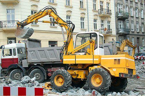 una ruspa gialla e un camion da lavoro in una strada di citta' e vista delle macerie