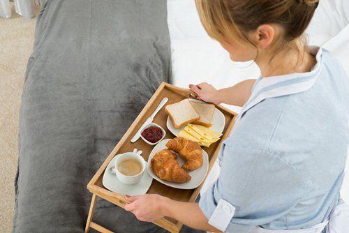 cameriera porta il vassoio con colazione in camera